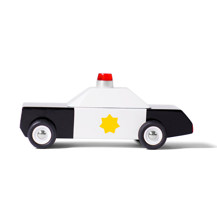 A toy car in the style of an American police car. Featuring gold star on the door and siren mounted on top.