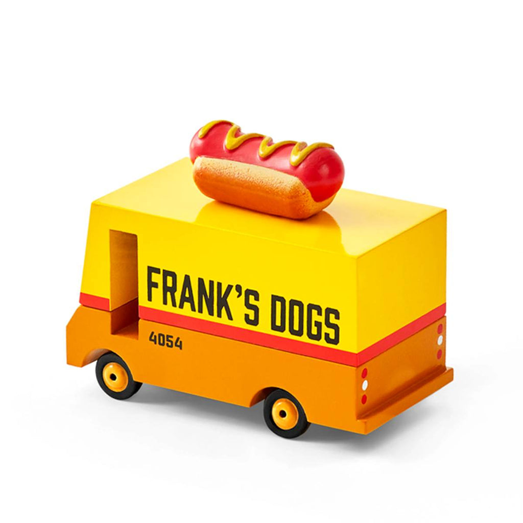 "A miniature wooden toy van. Created to  mimic New York Hot Dog Food trucks, it features the slogan ""Frank's Dogs"" is painted in red orange and yellow, and has a miniature hot dog on its roof."