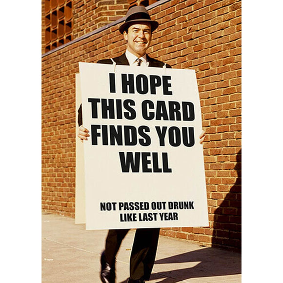 "A humorous greeting card featuring photograph of a man holding a placard sign.. The text reads ""I hope this card finds you well..... not passed out drunk like last year"""