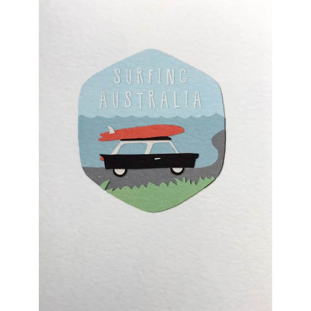 "A white greeting card featuring a illustration of a car with a surfboard on top. The text reads "" Surfing Australia""."