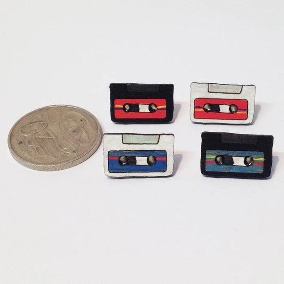 A pin style brooch depicting a retro cassette tape. Made from bamboo wood and hand painted. Shown on a polka dot background.