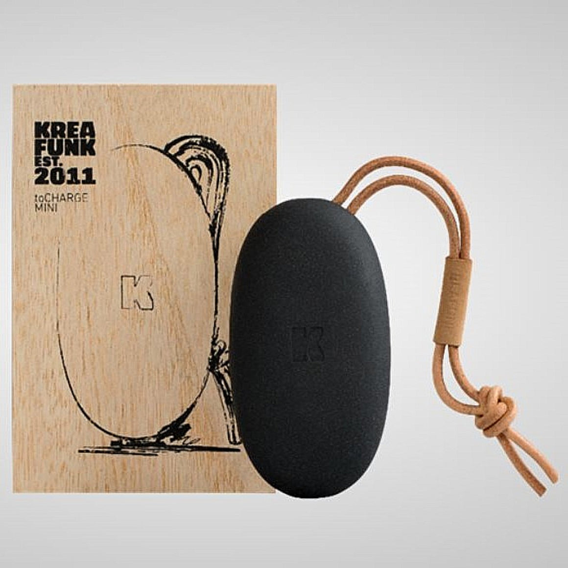 A small pebble shaped power bank in black with a tan leather strap. Shown in front of its natural wood box.