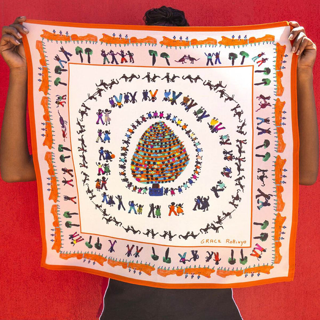 A colourful silk scarf featuring Dancing at Christmas by Grace Robinya. Rings of children, adults, animals, trees and rocks encircle a large and highly decorated Christmas tree.