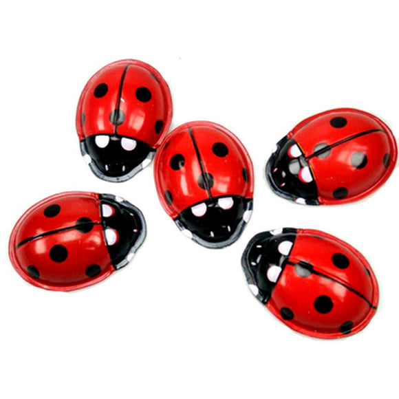 A group of five tin toy ladybirds in red white and black  viewed from above.