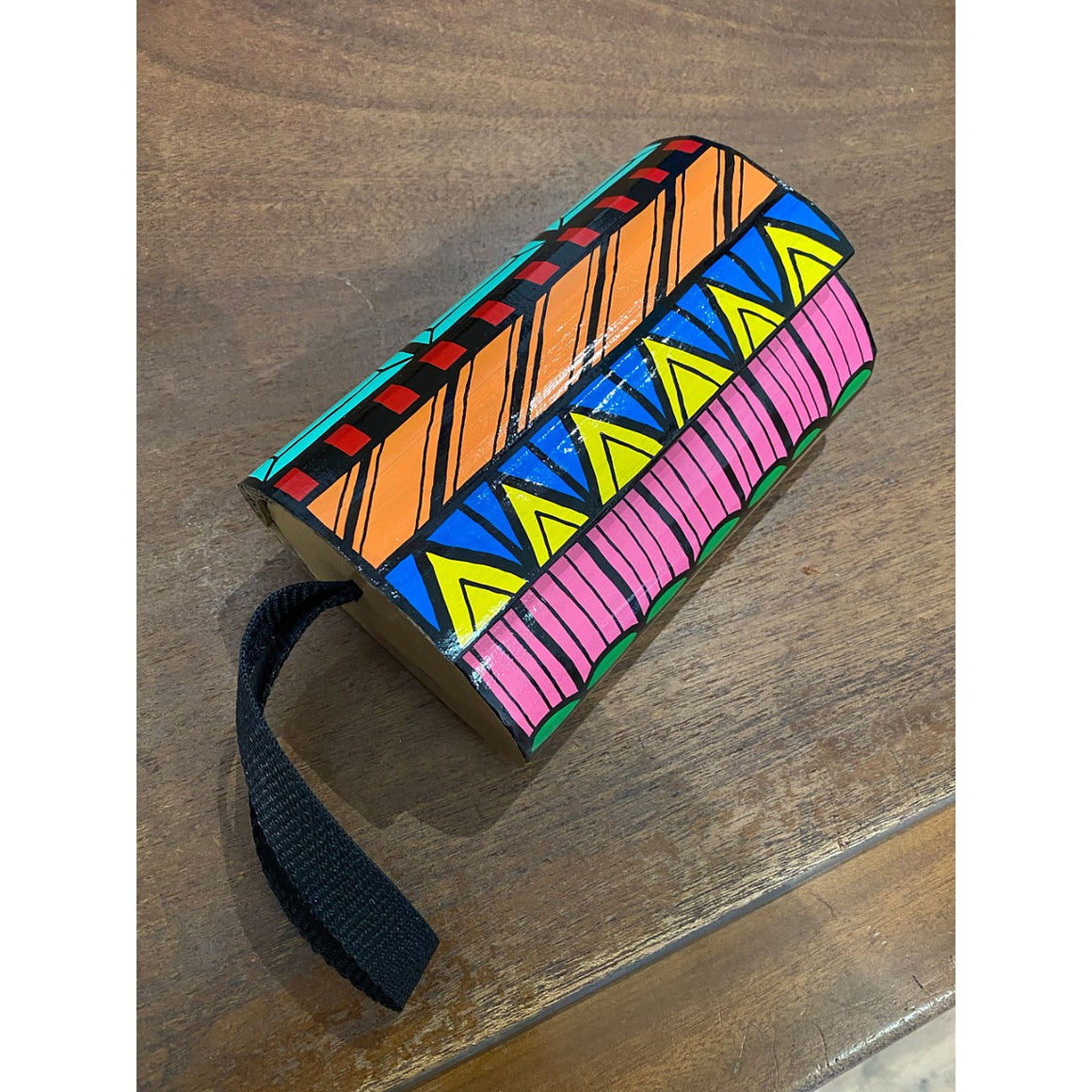 A brightly coloured and patterned clutch bag made by Jeff McCann featuring a black wrist strap. Displayed on a wooden surface,
