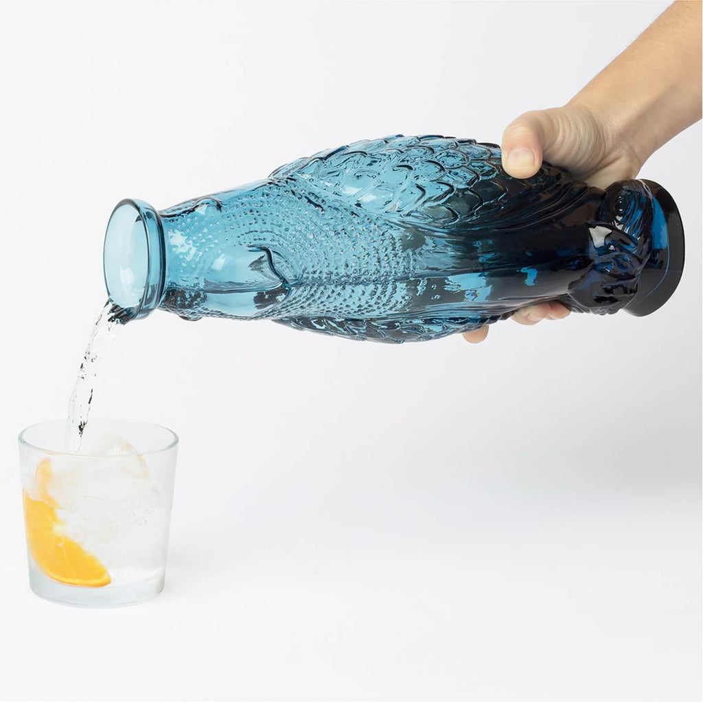 A blue cockatoo shaped glass carafe shown pouring water into a glass