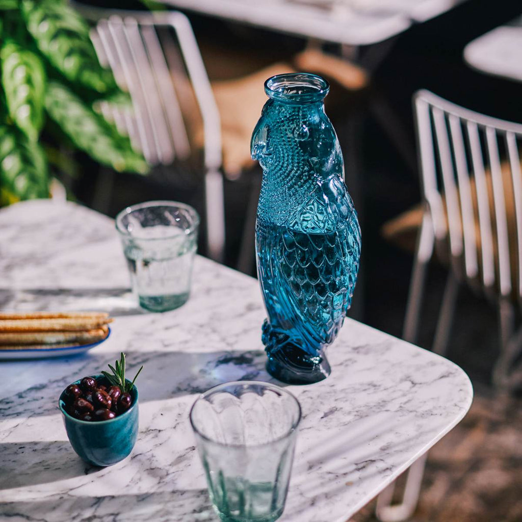 A glass cockatoo carafe shown on a outdoor table surrounded by drinks and snacks.
