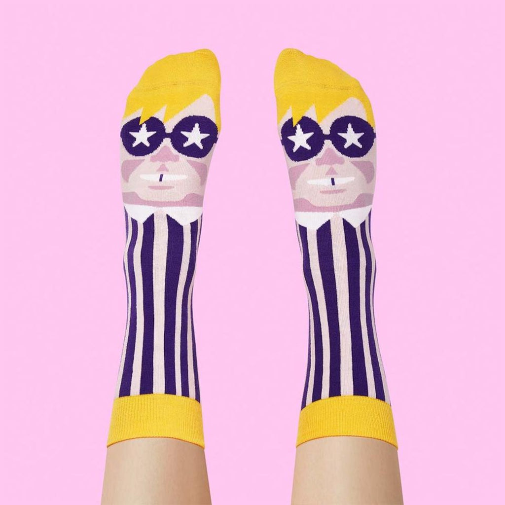 Image of a pair of feet which are wearing a pair of socks which feature a graphic illustration of Elton John