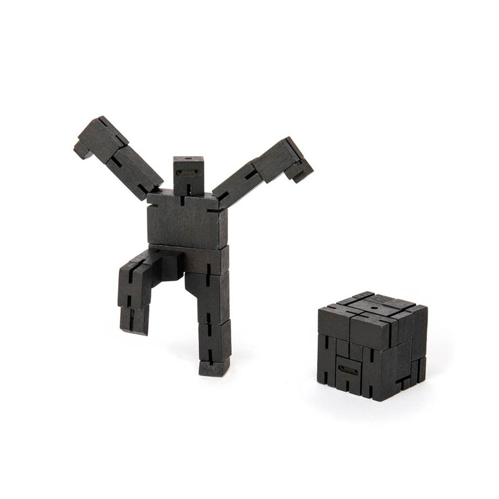 A wooden ninja robot puzzle toy made of multiple black interconnected wood pieces. Shown in a ninja pose. Shown Standing next to another robot puzzle, folded up into a cube.