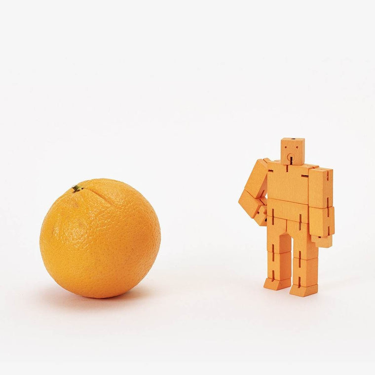 A wooden robot puzzle toy made of orange interconnected wood pieces. Shown Standing next to an orange