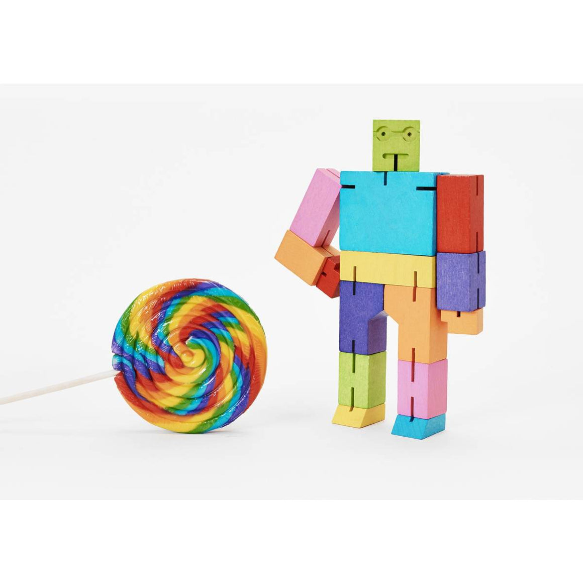A wooden robot puzzle toy made of multicoloured interconnected wood pieces. Shown Standing next to a rainbow lollipop.