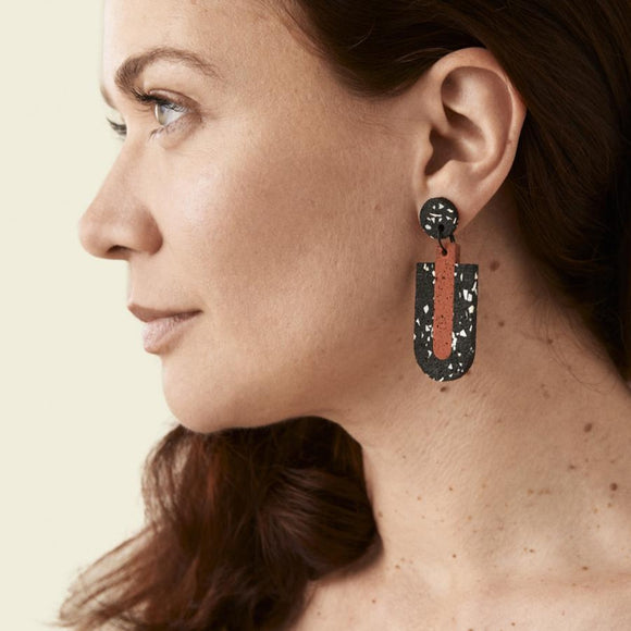 Image featuring a pair of two individual earrings which have a rubberized texture and hold the colours black, white and red