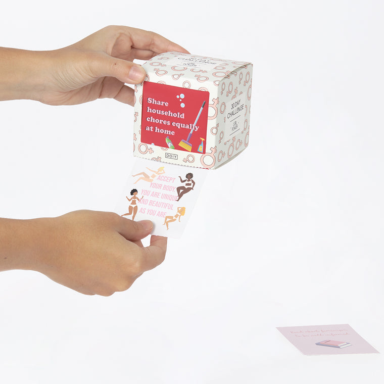 An activity box containing girl power prompts is shown. A hand is shown holding one of the 30 prompt cards contained inside the box.