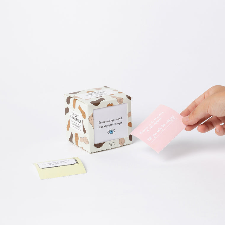 An activity box containing self confidence prompts is shown. A hand is shown holding one of the 30 prompt cards contained inside the box.