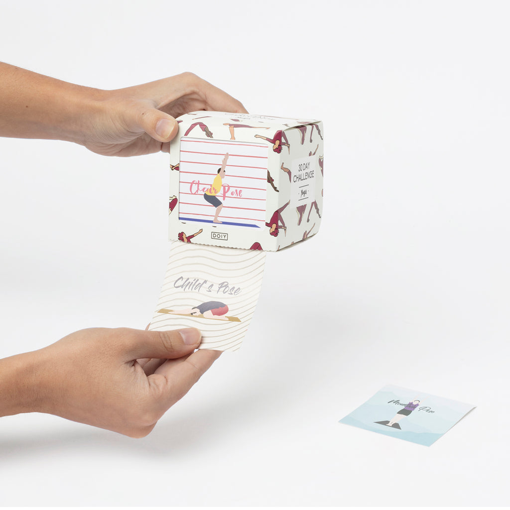 An activity box containing Yoga pose prompts is shown. A Hand is shown holding one of the 30 prompt cards contained inside the box.