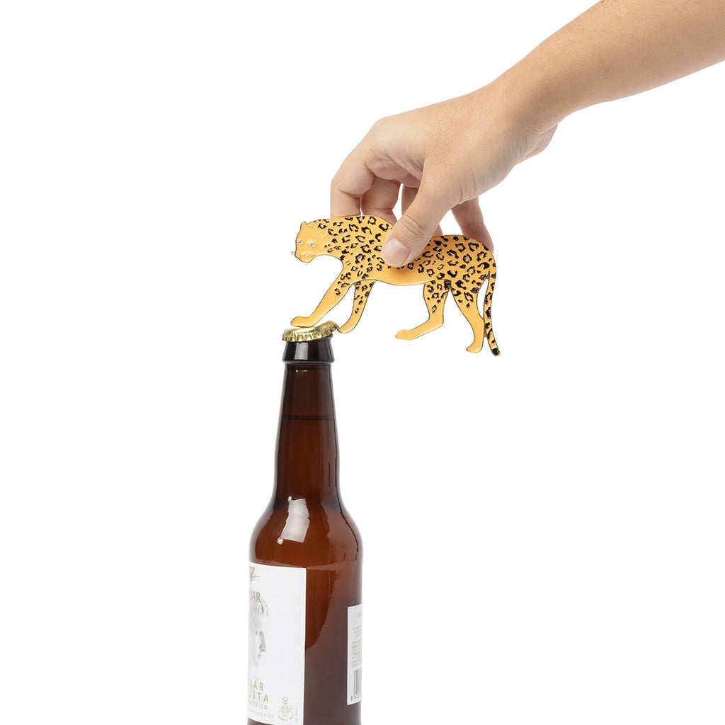 A cheetah shaped bottle opener is shown opening a beer bottle. The legs of the cheetah function as the bottle opener