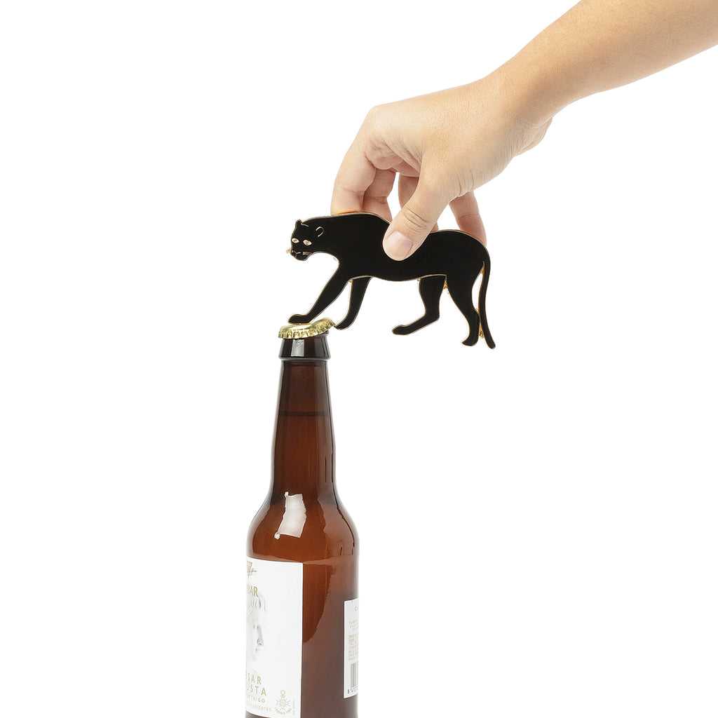 A panther shaped bottle opener is shown opening a beer bottle. The legs of the panther function as the bottle opener