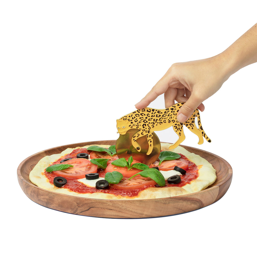 A cheetah shaped pizza cutter is shown cutting a pizza on a wooden plate