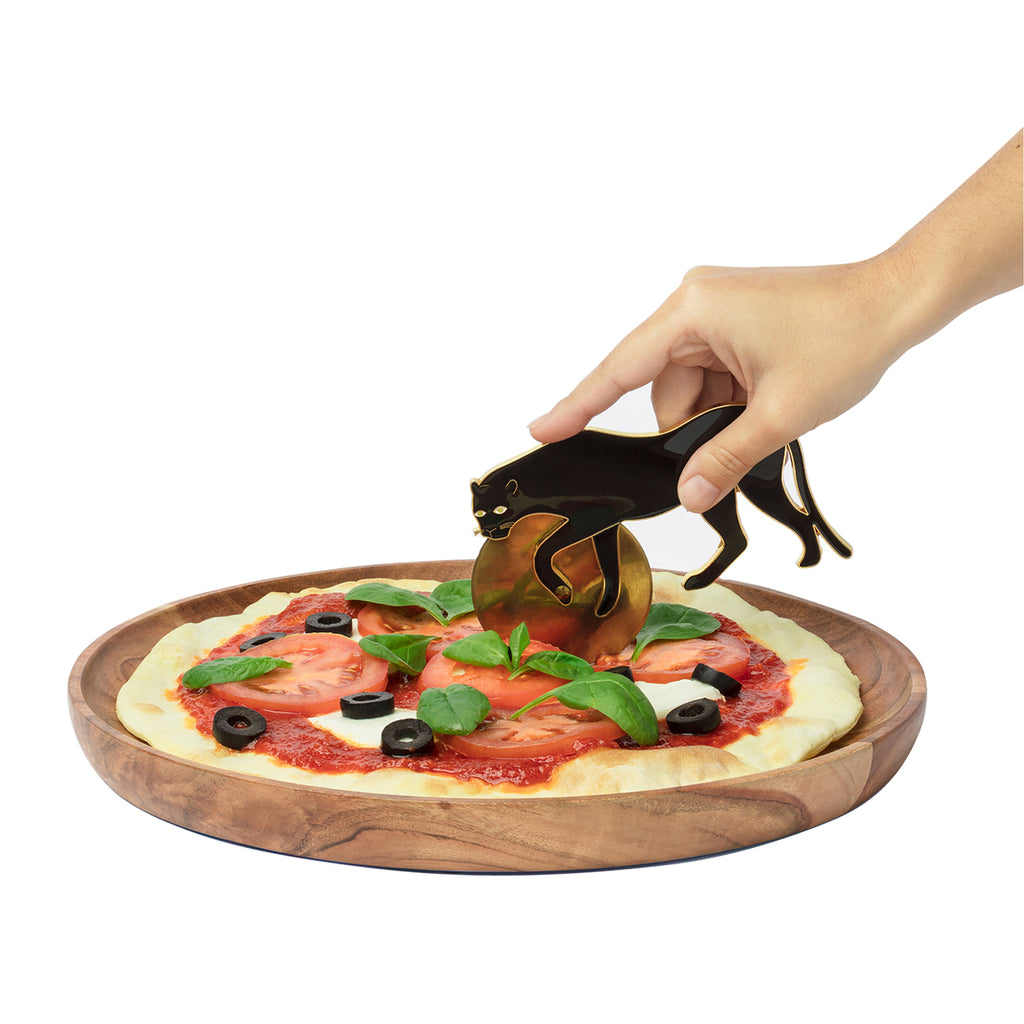 A panther shaped pizza cutter is shown cutting a pizza on a wooden plate