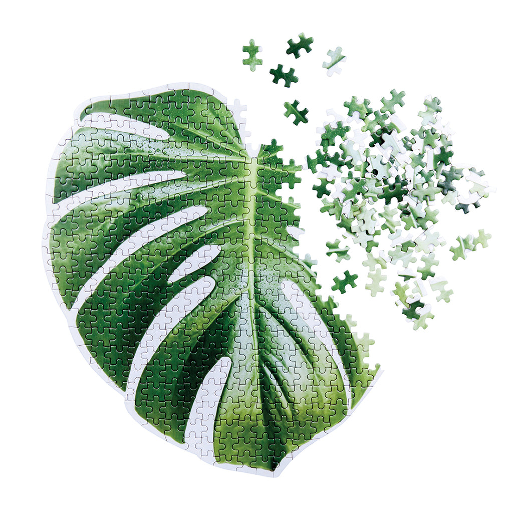 A  puzzle in the shape and print of a green Monstera rainforest plant leaf. Shown almost complete.