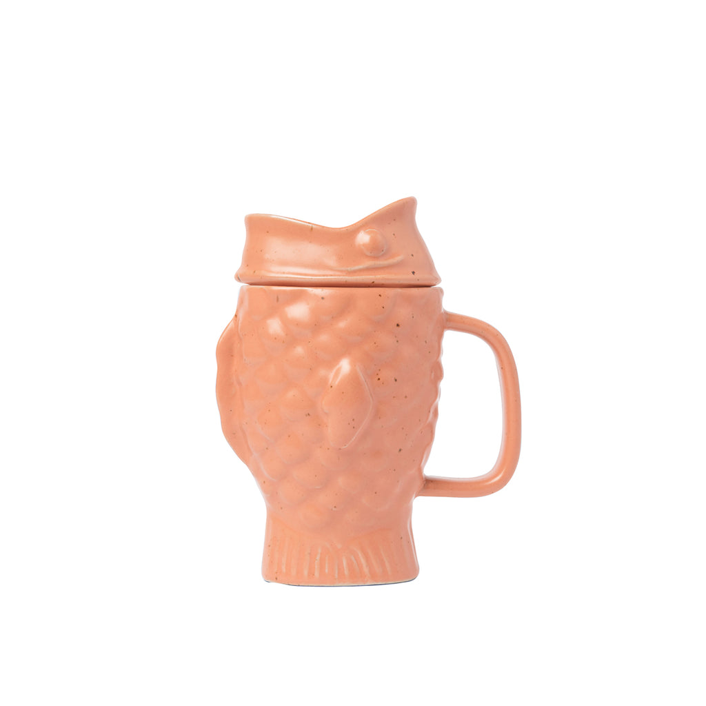 A pastel peach pink Dolomite ceramic mug shaped like a Japanese taiyaki cake (a waffle cake with filling, shaped like a fish). The glaze is lustrous matte and slightly speckled.