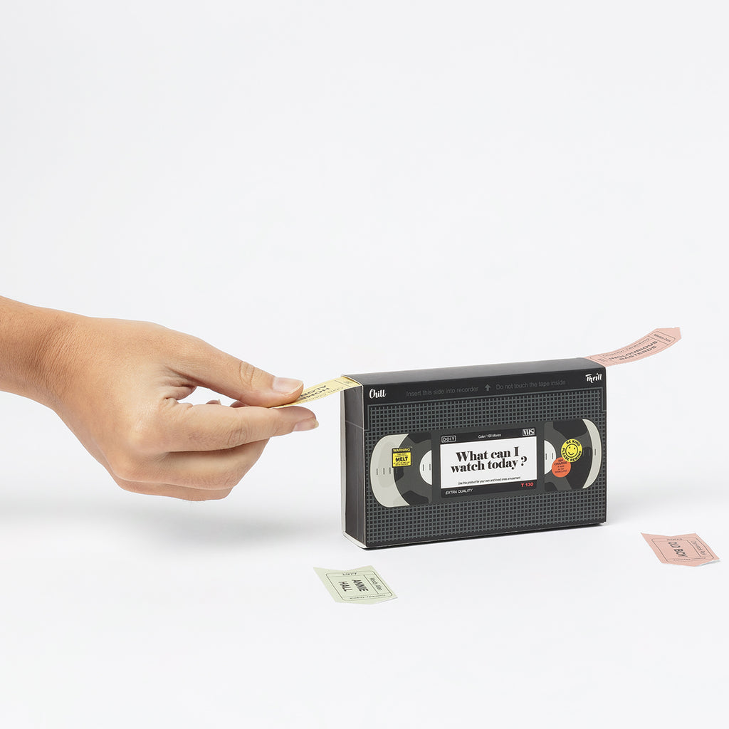 A box that dispenses issues tickets from two sides and is shapes like a VCR tape. On one side tickets are dispensed labelled Chill, on the other side tickets are dispensed that are labelled Thrill, A hand is selecting a ticket from the box.