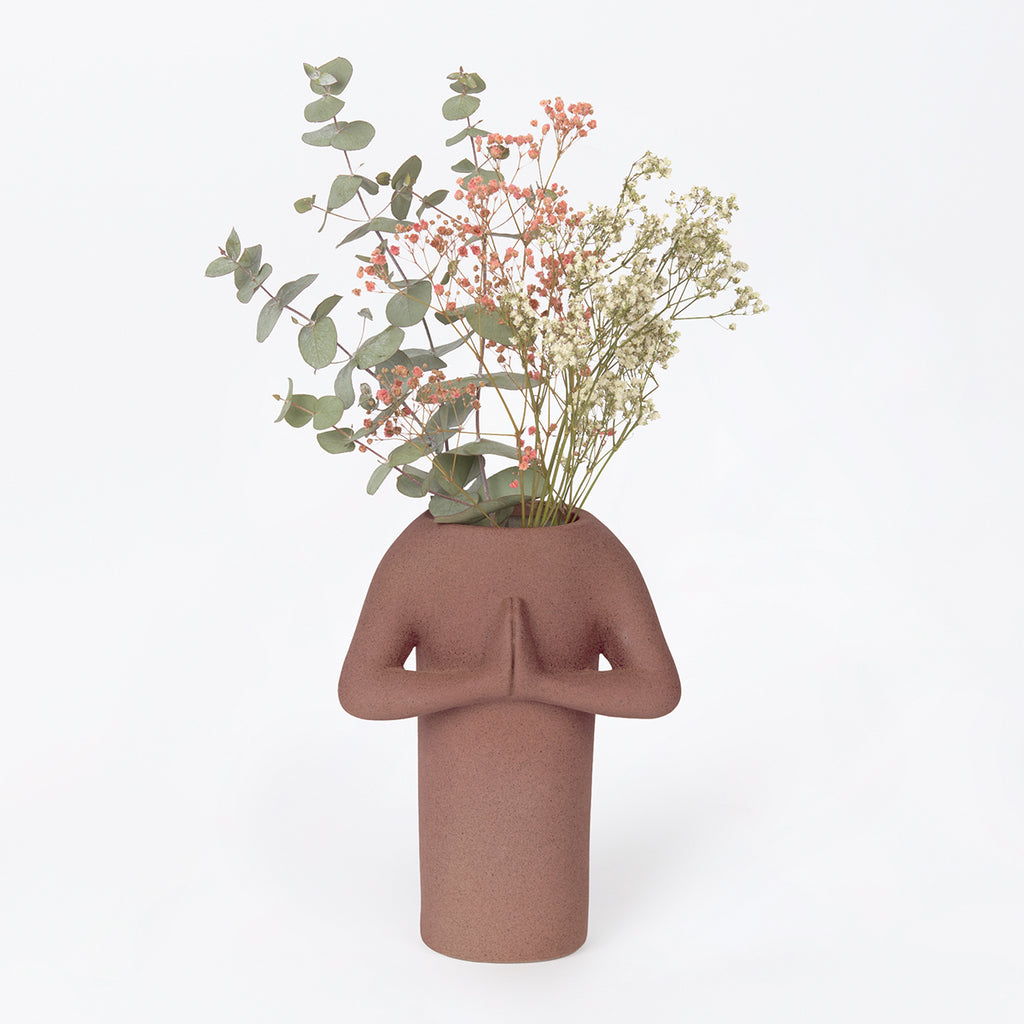 A brown ceramic vase in the form of a simplified figure in the namaste pose with palms together. The opening to the vase is in place of the head, and is shown with Australian wldflowers
