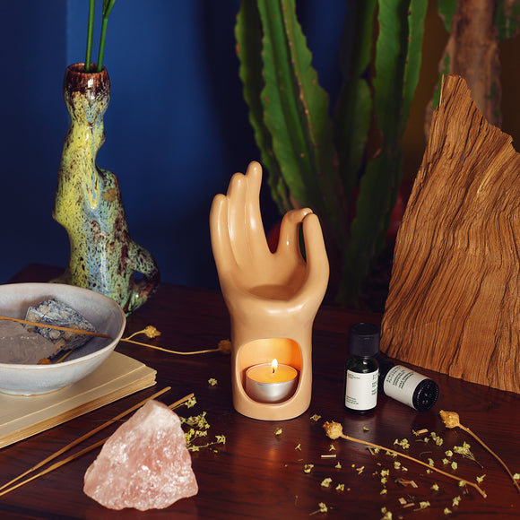 An essential oil burner in the shape of a hand in the Yoga pose of mudra. A tea light fits in a hollow within the wrist and the oil is placed in a well in the palm of the hand.