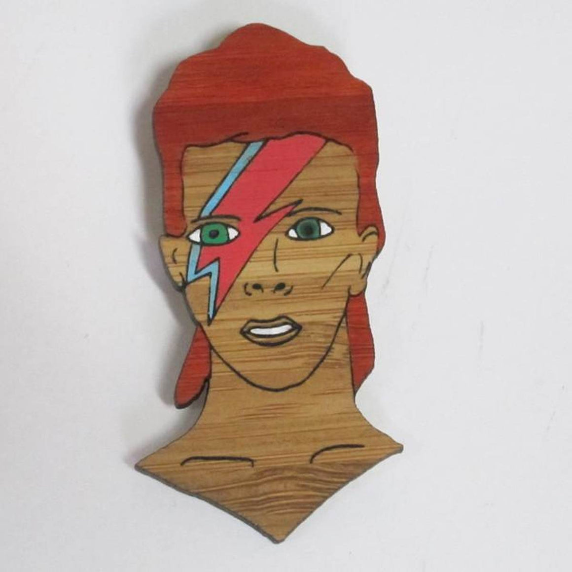 A brooch featuring a portrait of singer songwriter David Bowie. He is shown from the neck up, with his iconic red hair and a blue and red lightning bold painted across his face..Made from bamboo wood and hand painted.