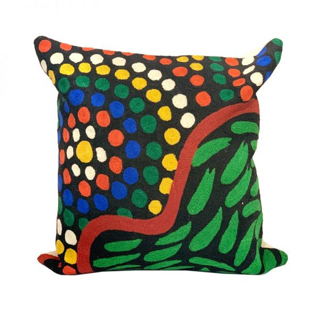 An embroidered wool Cushion featuring an Aboriginal Artwork in Green, yellow, orange, cream and blue tones on a black background. A wavy line divides the design, one side featuring concentric dots in a variety of colours; the other side features green seed shapes.