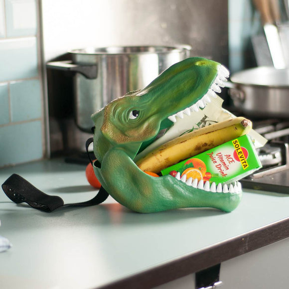 "A children's lunch box or storage case in the shape of a Green Tyrannosaurus Rex Head, Shown closed with the carry strap attached, which appears like a harness for the dinosaurs head. Attached tag read "" DINO CASE : Keep your goods in safe fangs"""