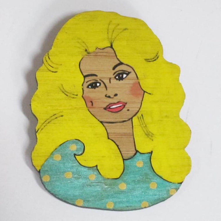 A brooch featuring a portrait of singer songwriter Dolly Parton. She is shown wearing a green top with Yellow polka dots.Made from bamboo wood and hand painted.