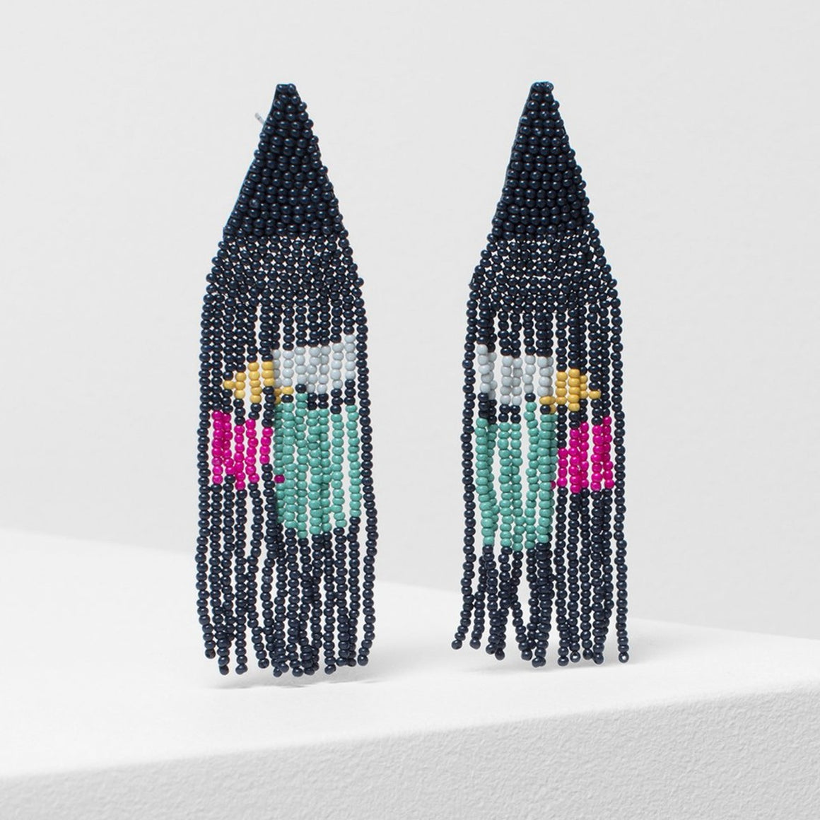 A densely beaded pair of drop earrings consisting of a woven beaded triangle in tiny navy beads and a multi colour fringe.,