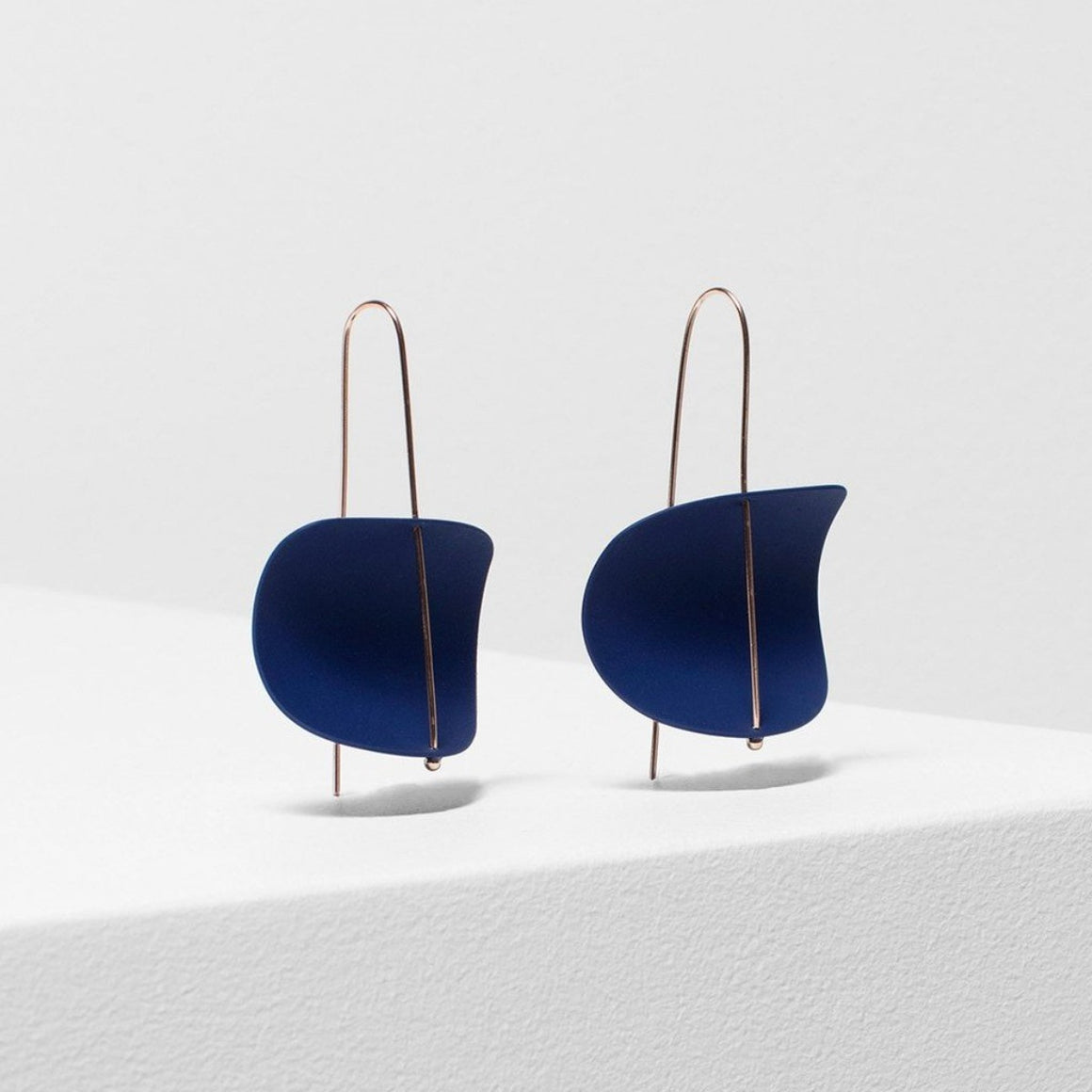 Image featuring two cobalt blue rubber earrings with a rose gold bar through the centre