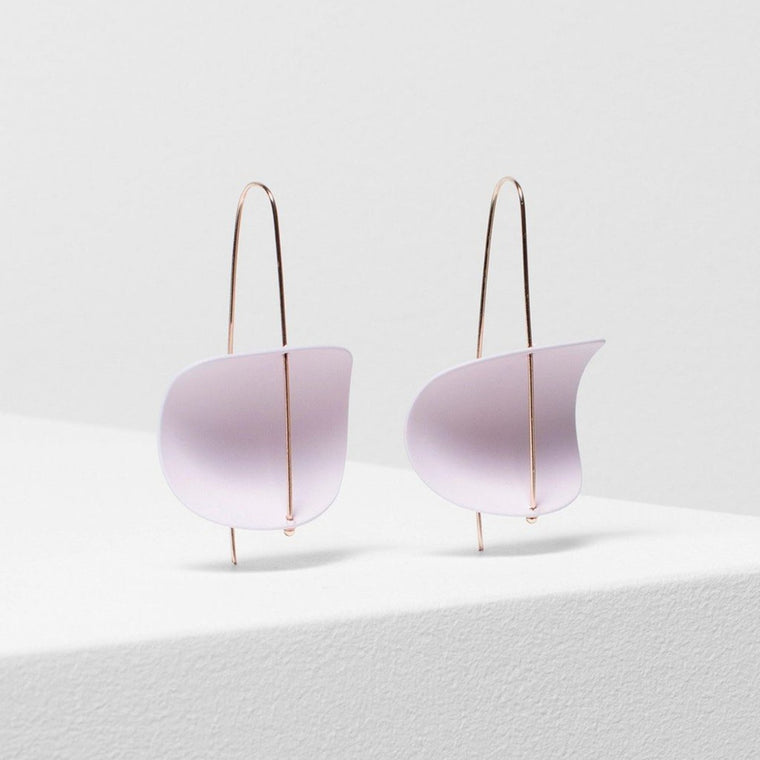 Image featuring a photograph of two blush rubber earrings with a rose gold bar hanging through the centre