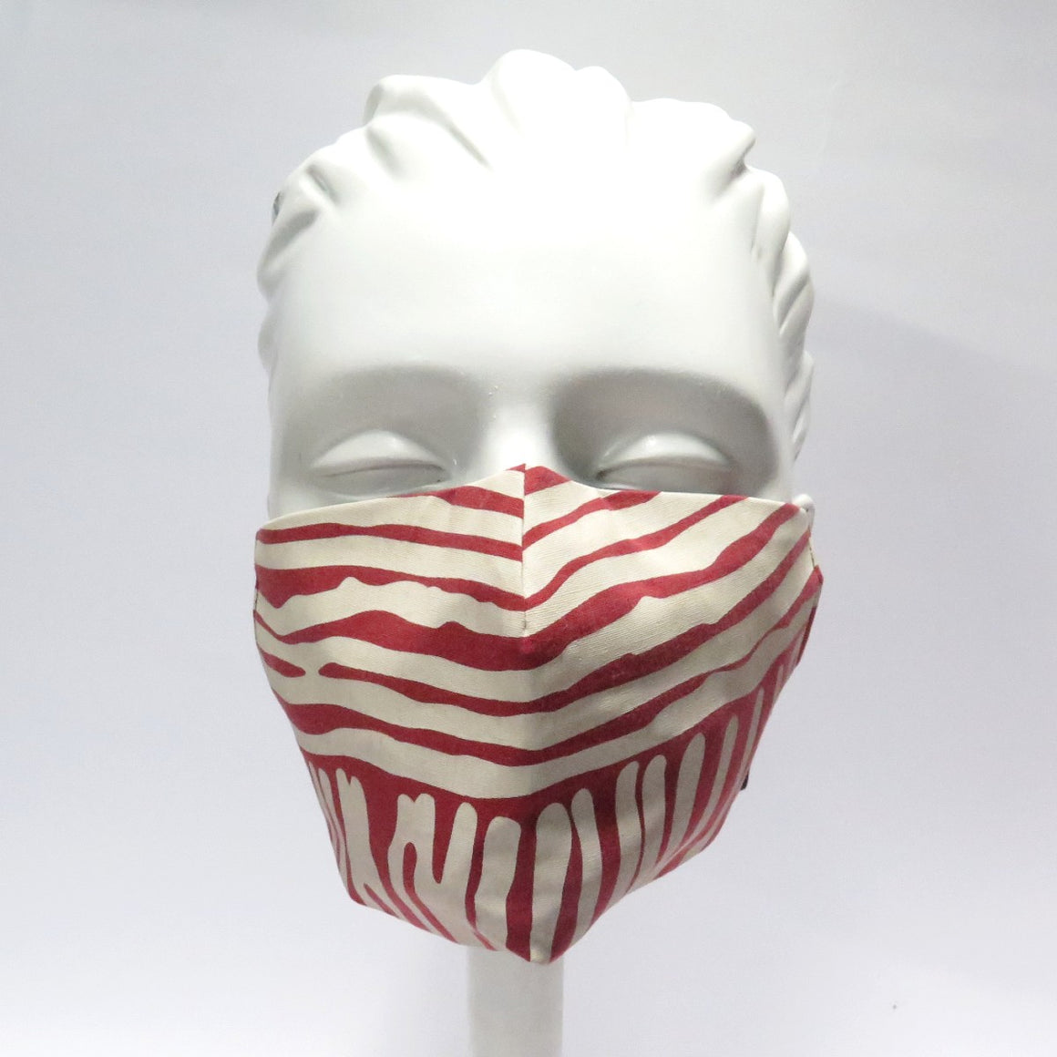 A mannequin is shown wearing a facemask made from fabric designed by artist Eunice Napanangka Jack. The fabric consists of white stripes on a deep red base.