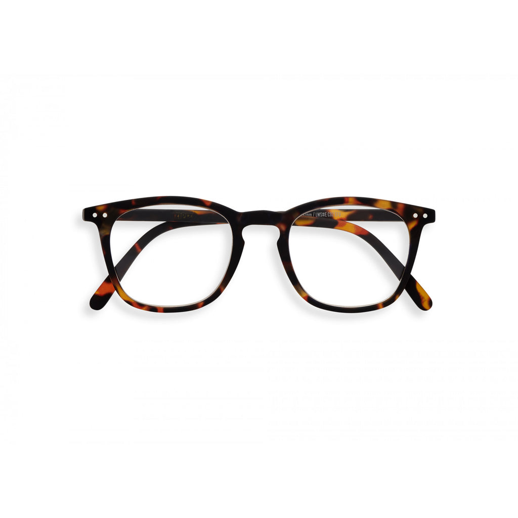 A pair of magnifying reading glasses. The frames are a large, structured, trapezium shape in a mottled classic tortoise shell finish.