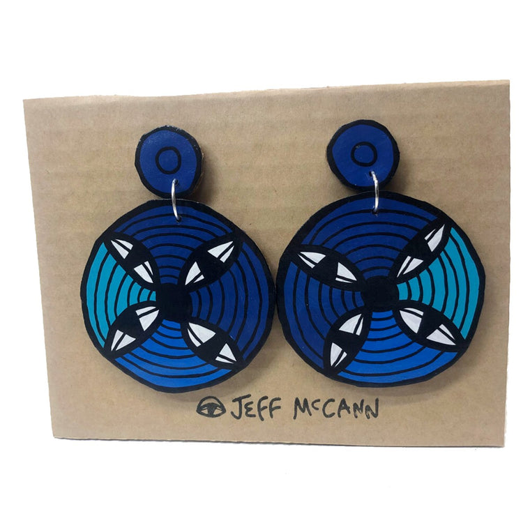 A Pair of Drop Earrings made of hand painted cardboard. A geometric design in the shape of a circle each containing 4 eyes - in blue tones and white.