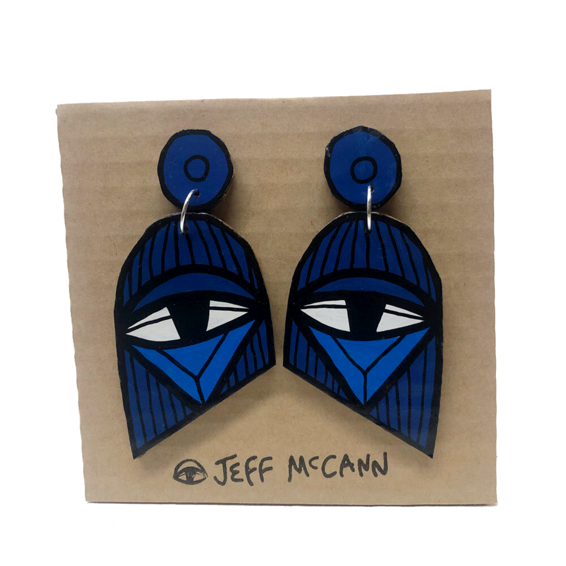 A Pair of Drop Earrings made of hand painted cardboard. A geometric design in the shape of two eyes in orange within an abstract geometric shape - in blue tones and white.