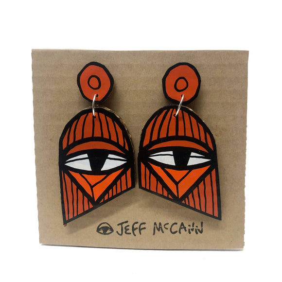 A Pair of Drop Earrings made of hand painted cardboard. A geometric design in the shape of two eyes in orange within an abstract geometric shape - in orange tones and white.