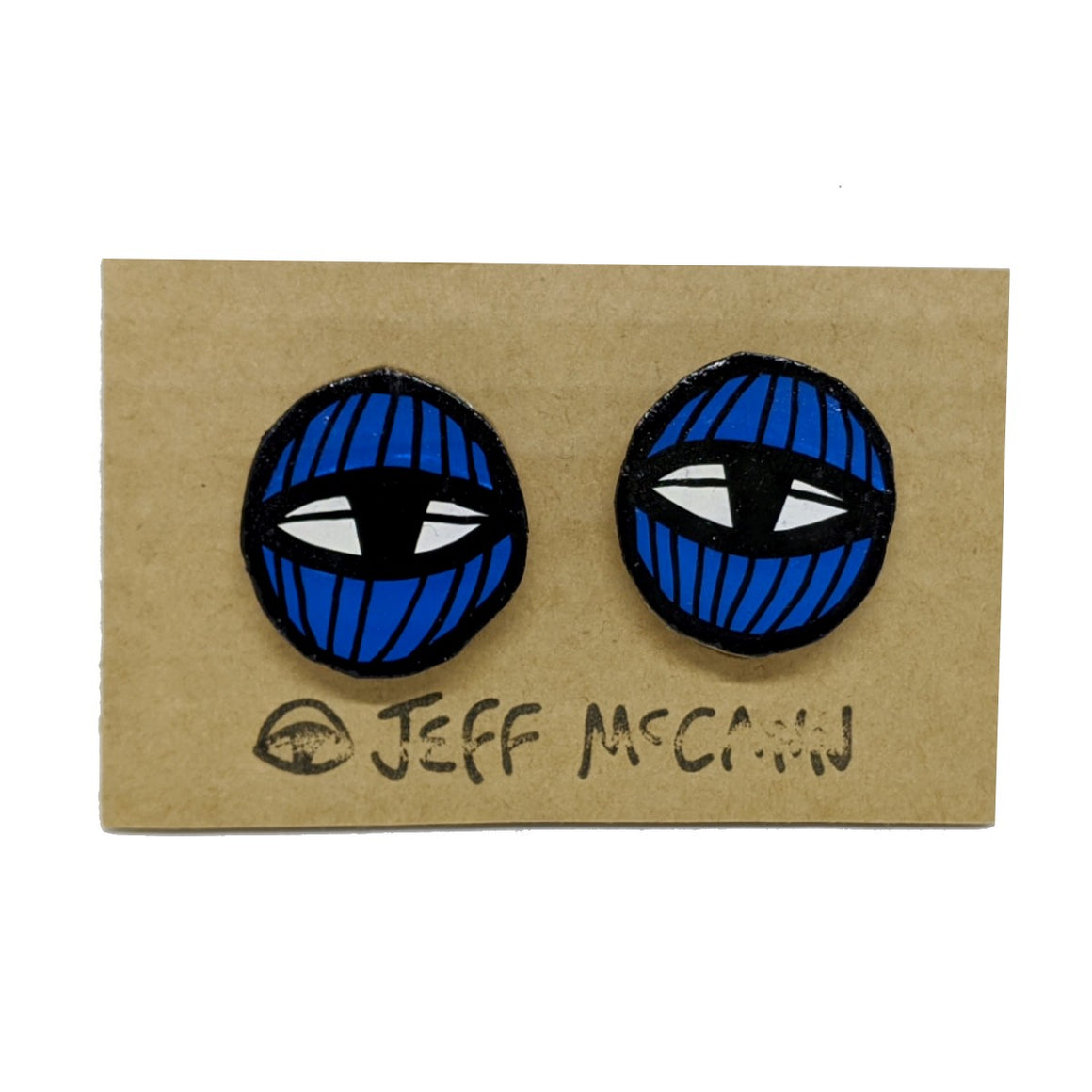 A Pair of stud Earrings made of hand painted cardboard. A geometric design in the shape of two eyes in blue and white.