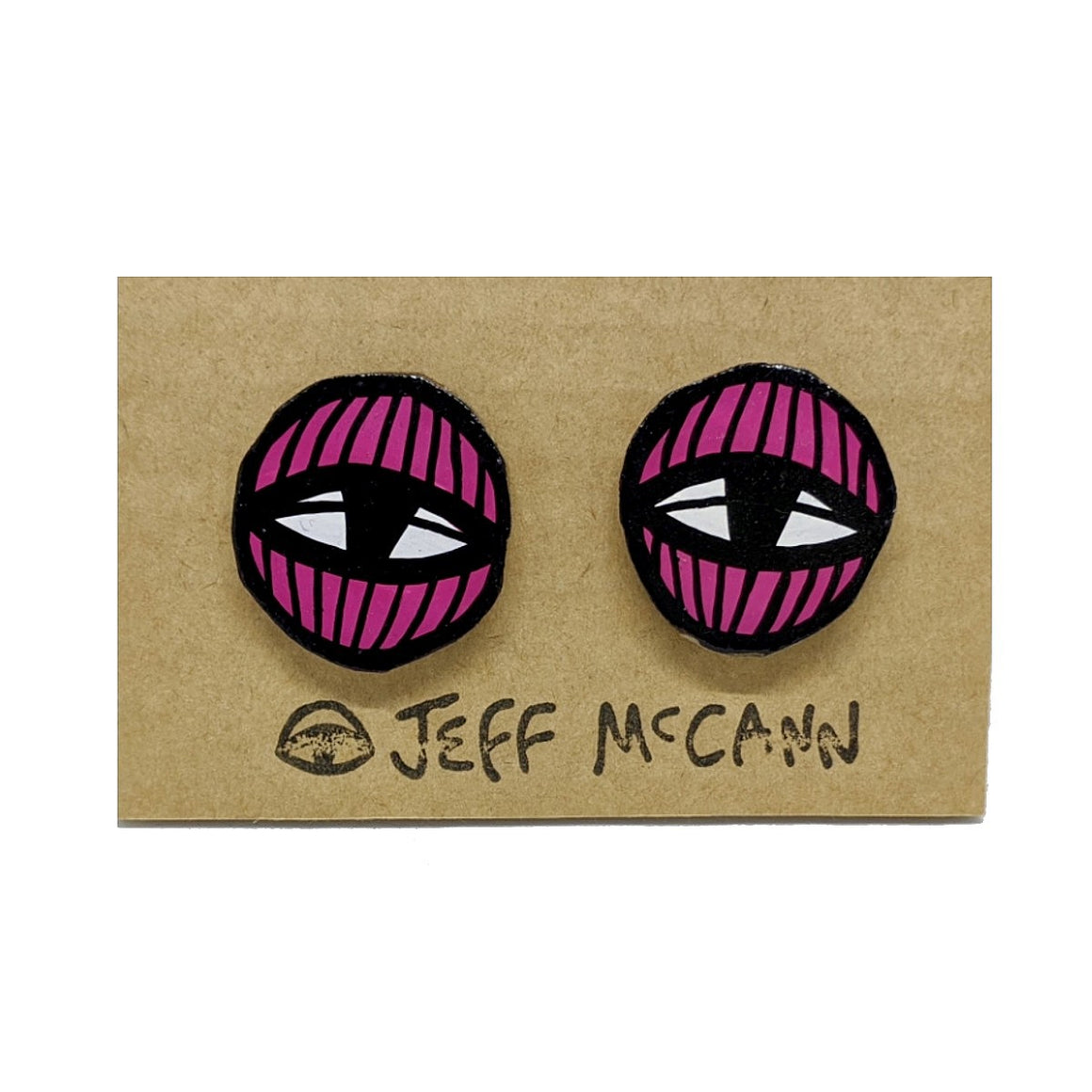 A Pair of stud Earrings made of hand painted cardboard. A geometric design in the shape of two eyes in pink and white.