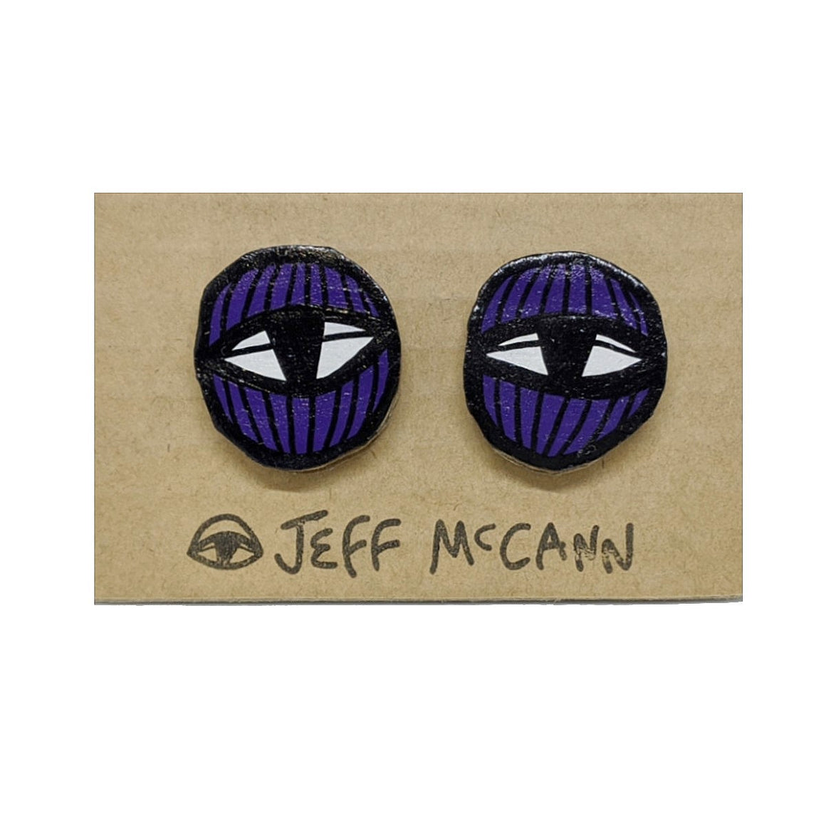 A Pair of stud Earrings made of hand painted cardboard. A geometric design in the shape of two eyes in purple and white.