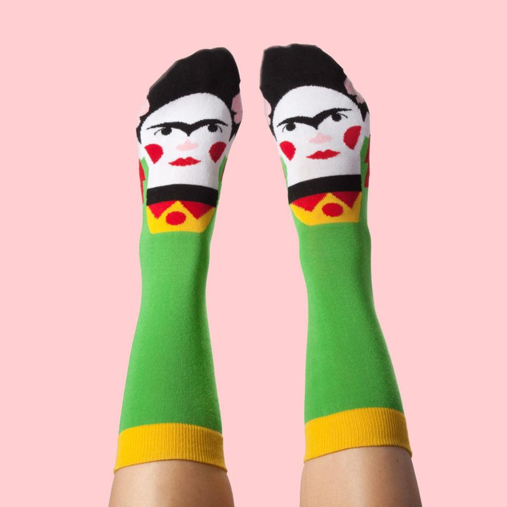 Image featuring a pair of feet that are wearing a pair of graphic illustrated socks with frida kahlo on them