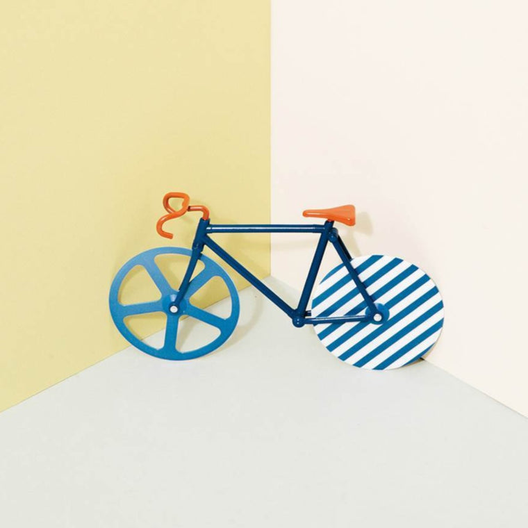 A pizza cutter in the shape of a bicycle shown against contrasting colours. The bicycles Wheels function as the pizza cutters. The item features blue and orange tones and blue stripe on of the a blue stripe on one of the bicycle wheels.
