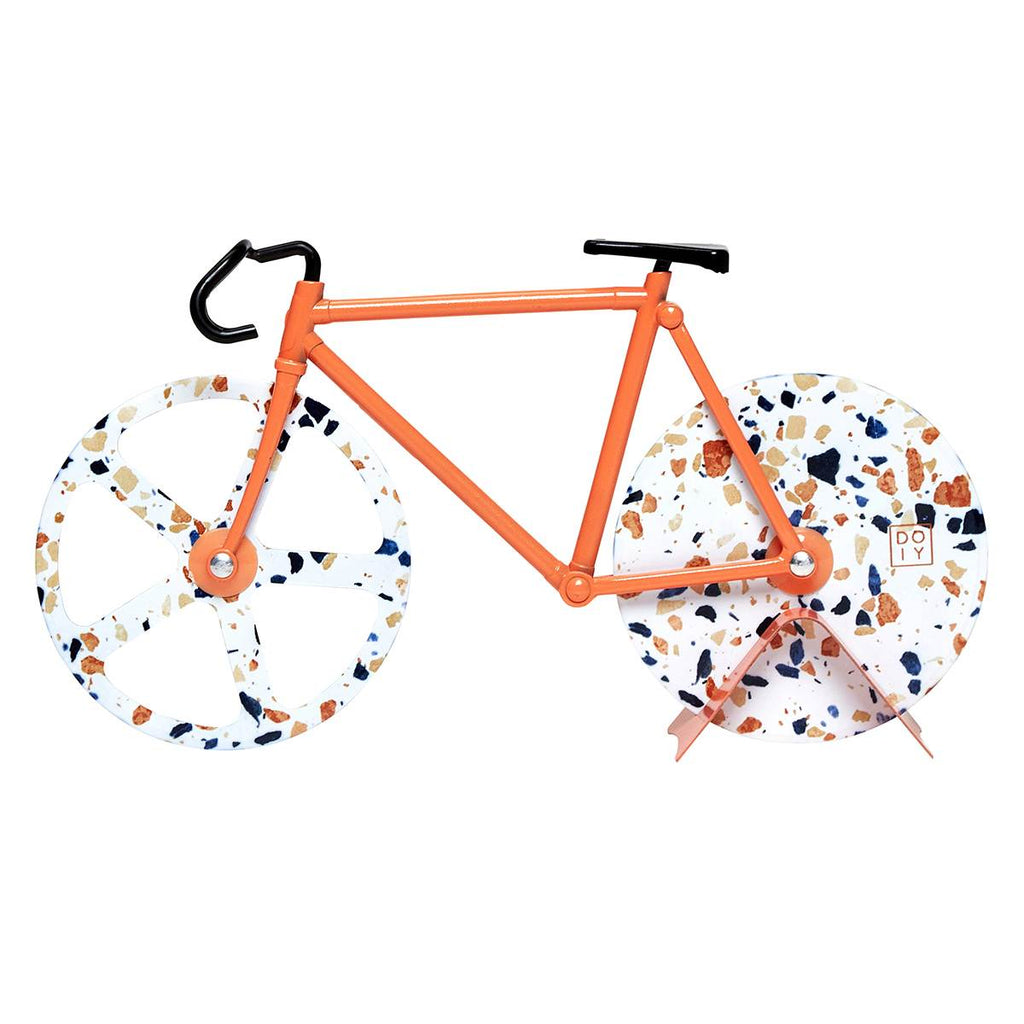 A pizza cutter in the shape of a bicycle featuring orange and black tones and terrazzo print on the wheels. The bicycles Wheels function as the pizza cutters.