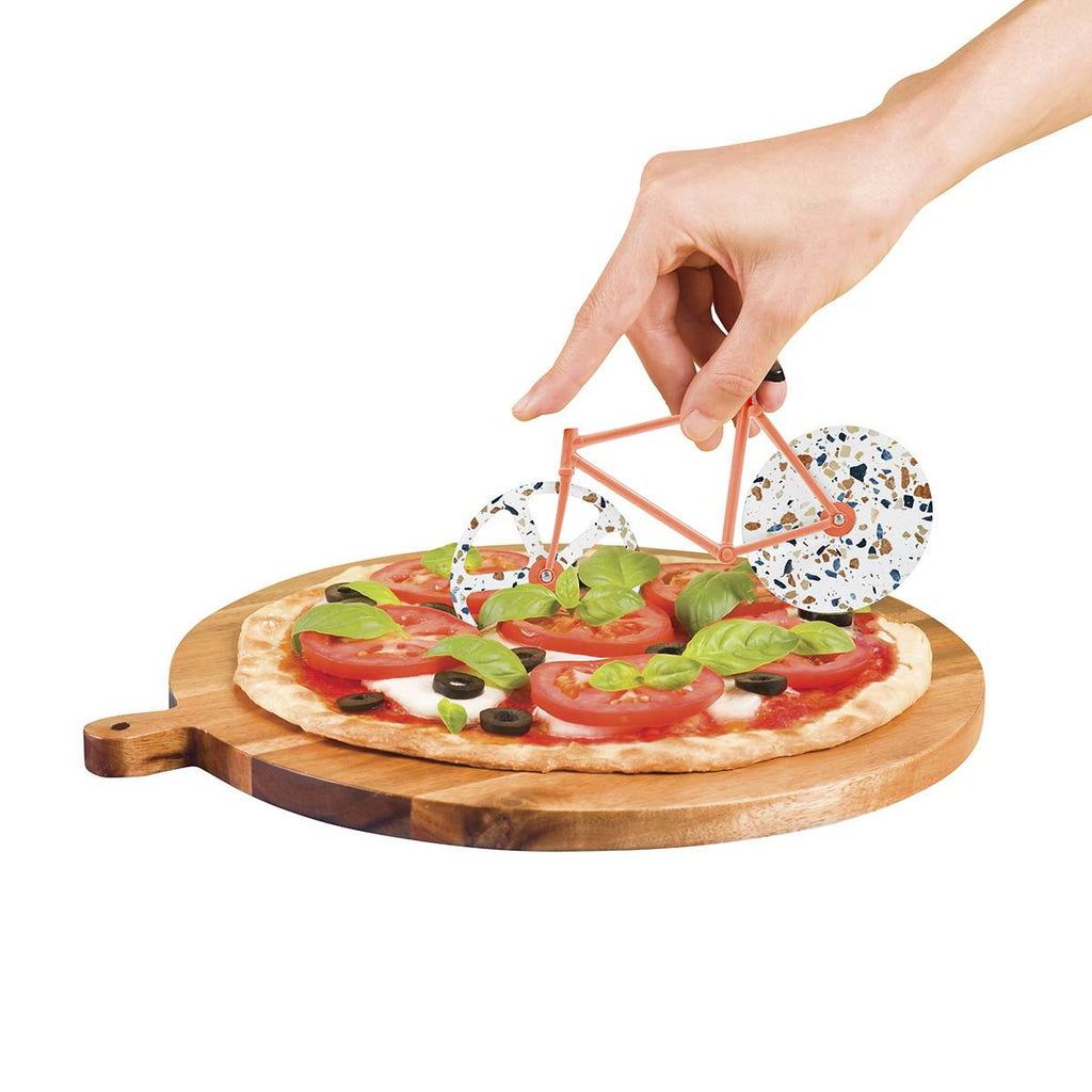 A terrazzo print toned bicycle shaped pizza cutter shown cutting a pizza on a breadboard.
