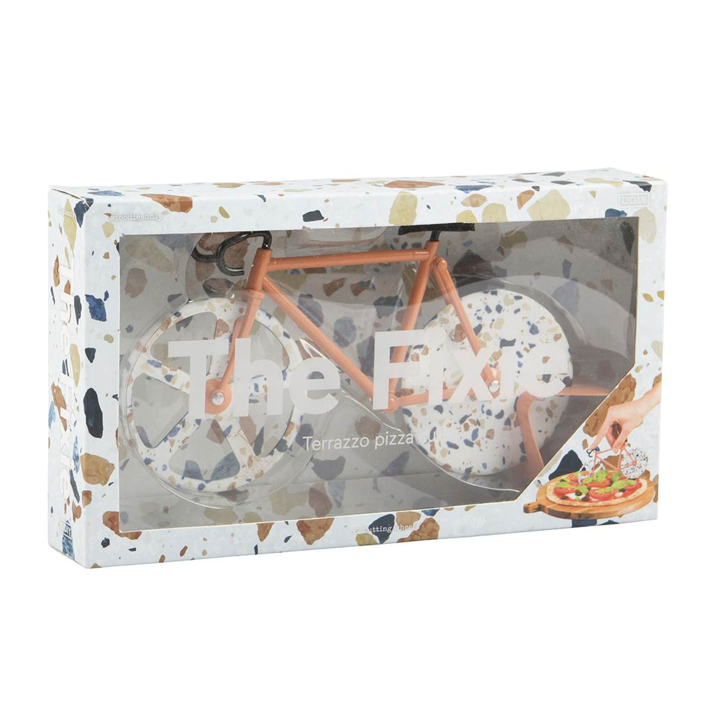 A terrazzo print bicycle shaped pizza cutter shown in attractive packaging with a matching print.