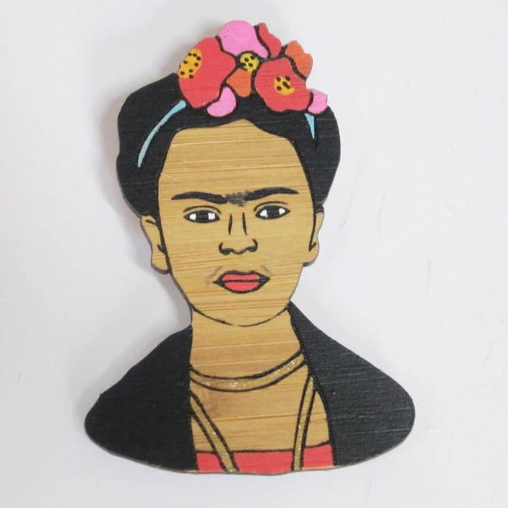 A brooch featuring a portrait of artist Frida Kahlo. Made from bamboo wood and hand painted.