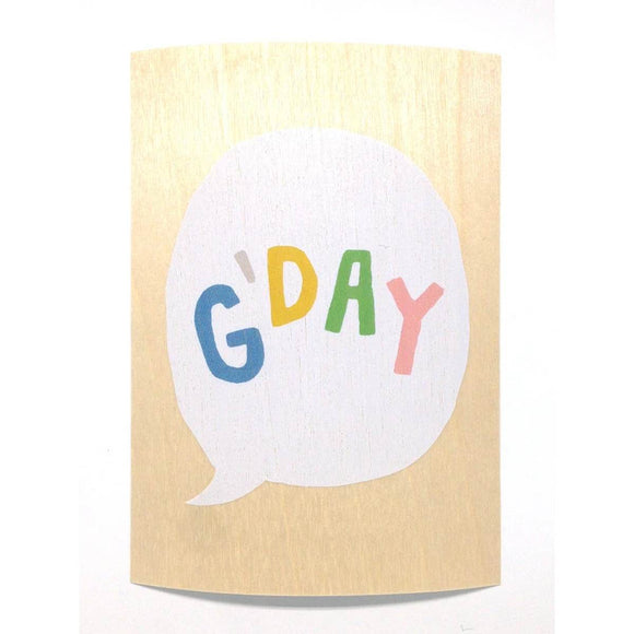 "A wooden postcard showing a speech bubble with the world ""G'DAY"" in colourful letters. The background is a natural light wood grain."